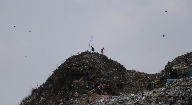Two men place a white flag on top of a rubbish heap following the disaster in Meetotamulla, on the outskirts of Colombo (AP Photo/Eranga Jayawardena)