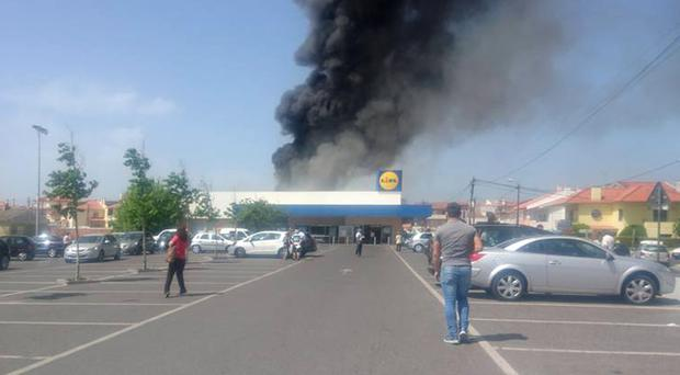 Photo taken with permission from the Facebook page of Fabio Miguel of smoke rising behind a Lidl supermarket near Lisbon, after a small plane crashed