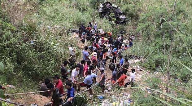 Volunteers use ropes to rescue survivors from the bus wreckage (Philippine Red Cross Nueva Vizcaya chapter/AP)