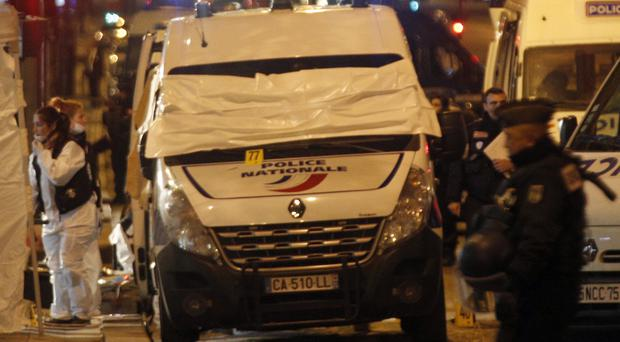 Forensic experts examine evidence from a police van on the Champs-Elysees (AP)
