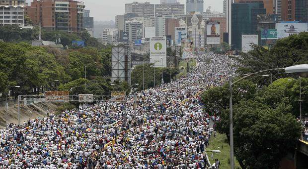 Anti-government protesters march along a highway in Caracas (AP)
