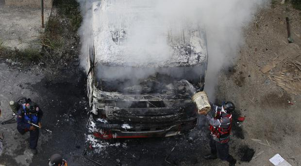 Firefighters put out a truck set on fire during anti-government protests in Caracas, Venezuela (AP)