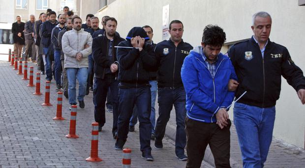 Police officers escort people suspected of links to US-based cleric Fethullah Gulen, in Kayseri, Turkey (Olay Duzgun/DHA-Depo Photos via AP)