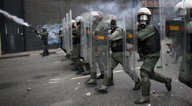 Bolivarian National Guards charge opponents of President Nicolas Maduro as they block protesters from reaching the national ombudsman office in Caracas, Venezuela (AP)