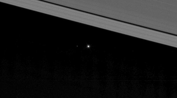Earth, visible as a pinprick of light between the mighty rings of Saturn, with the moon visible a short distance to the left of the planet