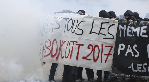 Youths shield behind a banner as Paris police firing tear gas