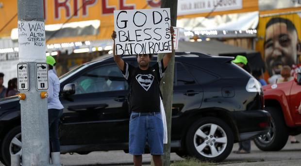 Everett Matthews holds up a sign outside the store where Alton Sterling was killed in Baton Rouge (AP)