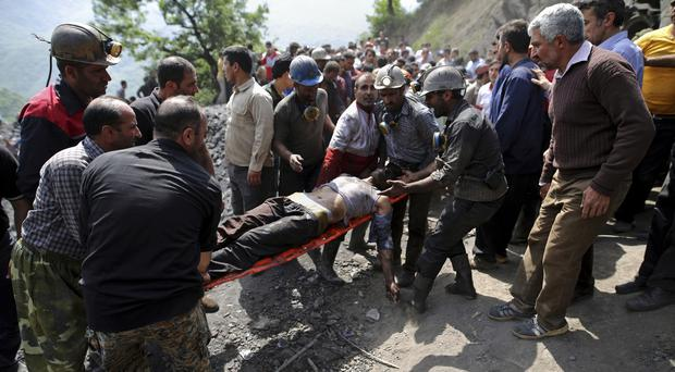 Rescue workers carry an injured miner from the mine near Azadshahr (Tasnim News Agency/AP)