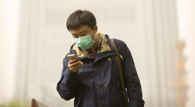 A man wears a face mask during a sandstorm in Beijing (AP/Mark Schiefelbein)
