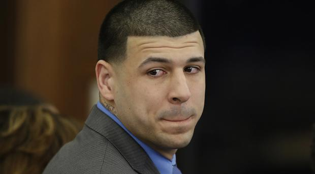 A report on the suicide of Aaron Hernandez has confirmed he wrote a reference to a biblical passage in ink on his forehead and in blood on the wall of his prison cell (Stephan Savoia/AP)