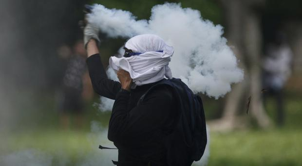 A student returns a tear gas canister fired by police at student protesters outside the Central University of Venezuela in Caracas (AP)