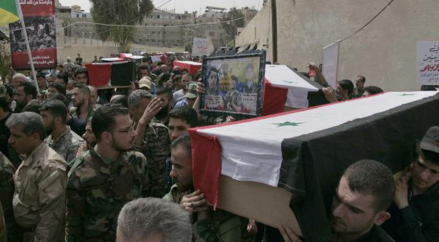 Mourners carry the coffins of more than 50 people killed in a recent car bomb attack in Damascus, Syria (SANA via AP)