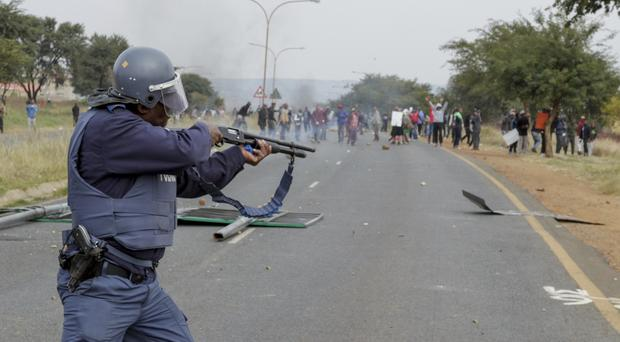 A police officer fires rubber bullets at protesters in Johannesburg (AP)
