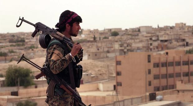 A fighter from the Syria Democratic Forces carrying weapons as he looks towards the northern town of Tabqa, Syria (Syrian Democratic Forces, via AP)