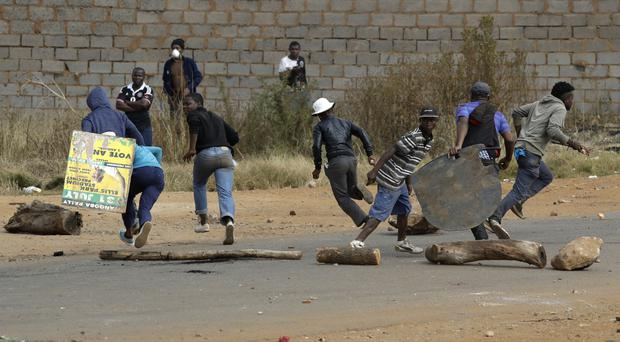 Protesters run for cover as police officers fire rubber bullets in Johannesburg, South Africa (AP/Themba Hadebe)