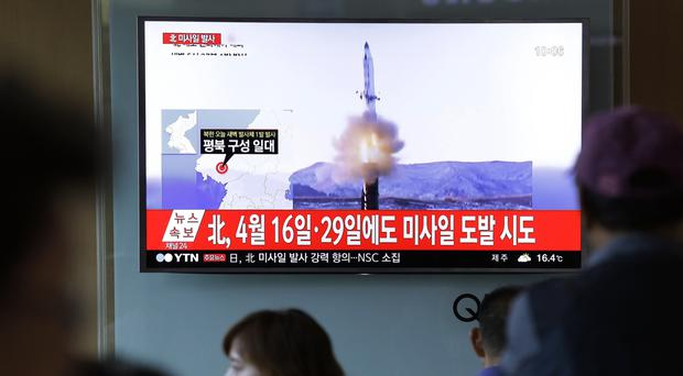 People at Seoul railway station watch a TV news programme showing a file image of a missile launch conducted by North Korea (AP Photo/Ahn Young-joon)