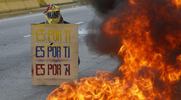 A demonstrator holds a sign that doubles a shield that reads in Spanish