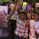 Supporters of Iranian president Hassan Rouhani cheer during a street campaign ahead the presidential election (AP)