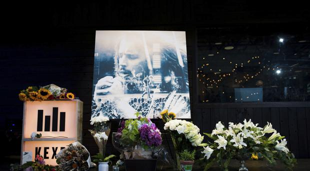 Flowers and cards sit in front of a large image with a depiction of Chris Cornell on it during a memorial in Seattle