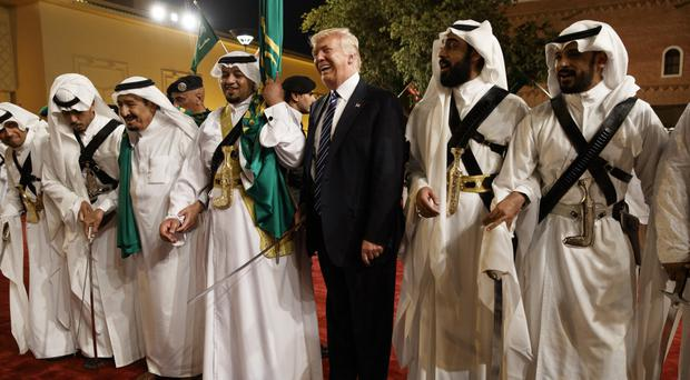President Donald Trump holds a sword and dances with traditional dancers during a welcome ceremony at Murabba Palace (AP)