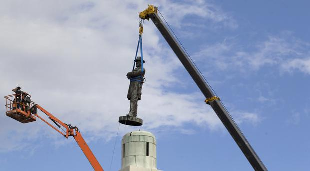 A statue of Confederate General Robert E Lee is removed from Lee Circle on Friday (AP)