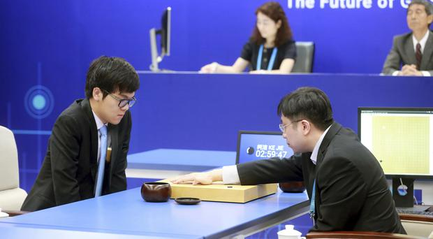 Chinese Go player Ke Jie (left) looks at the board as a man makes a move on behalf of Google's artificial intelligence program, AlphaGo (Chinatopix via AP)
