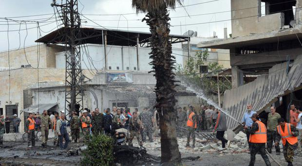 Syrian security forces and firefighters gather at the scene of an explosion in the central city of Homs (Sana/AP)