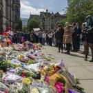 People look at flowers outside the Town Hall in Albert Square, Manchester after a suicide bomber killed 22 people