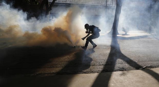 A protester retrieves a tear gas canister from security forces blocking an opposition march in Caracas (AP)