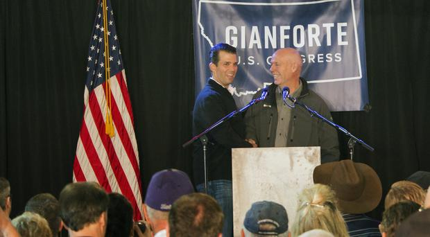 Republican Greg Gianforte, right, welcomes Donald Trump Jr onto the stage at a rally in East Helena, Montana (AP)