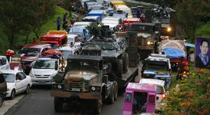 A military convoy passes gridlocked traffic outside Marawi city (AP)