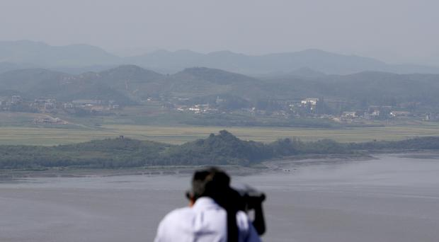 A visitor uses binoculars to see North Korean territory from the unification observatory in Paju, South Korea (AP)