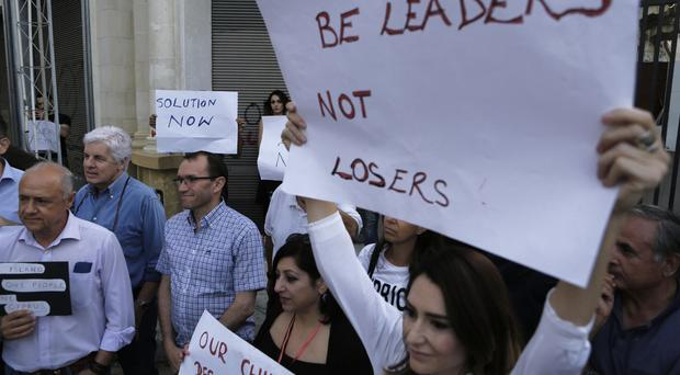 Mr Eide, third from the left, stands with Greek and Turkish Cypriots as they hold banners during a demonstration at the Ledras main crossing point inside the UN buffer zone dividing the Greek and Turkish Cypriot zones (AP)