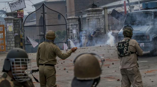 A masked Kashmiri protester runs for cover amid tear gas smoke fired by Indian policemen during a protest in Srinagar in Indian controlled Kashmir (AP Photo/Dar Yasin)