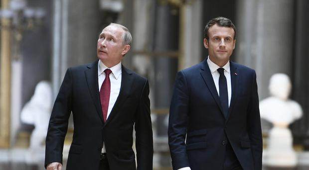 Emmanuel Macron and Vladimir Putin walk in the Galerie des Batailles at the Versailles Palace, near Paris (Stephane de Sakutin/Pool Photo via AP)