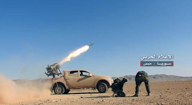 Syrian government troops fire rockets at insurgents in the province of Homs (Syrian Central Military Media/AP)