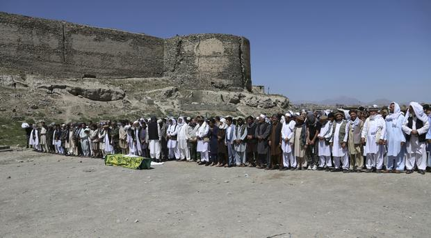 Afghans pray during the funeral of a victim of Wednesday's bombing in Kabul (AP)