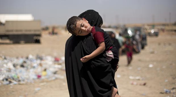 A child sleeps on his mother's shoulder after a perilous journey on foot to flee heavy fighting in Mosul (Maya Alleruzzo/AP)