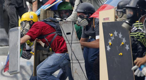Anti-government demonstrators clash with security forces in Caracas, Venezuela (AP)