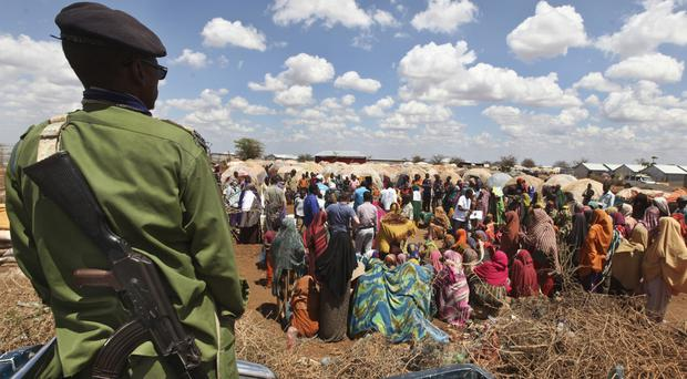 A Somali policeman provides security as displaced Somalis gather outside their makeshift shelters at a camp in Baidoa. (AP/Farah Abdi Warsameh)