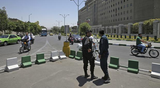 Police officers on guard as vehicles drive past Iran's parliament building in Tehran (AP/Vahid Salemi)
