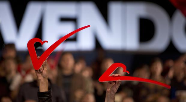 Supporters of the opposition party Vetevendosje hold up heart signs during the closing election campaign rally in Kosovo capital Pristina on Friday (Visar Kryeziu/AP)