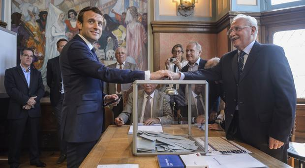 French president Emmanuel Macron casts his ballot in the first round of the two-stage legislative elections (Christophe Petit-Tesson/Pool Photo/AP)