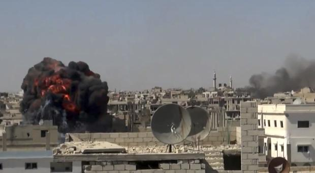 Smoke rises over buildings that were hit by Syrian government forces in Daraa (Nabaa Media, via AP)