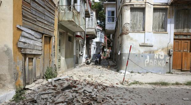 People look at the debris of a damaged building after an earthquake in the village of Plomari on the Greek island of Lesbos. (AP)