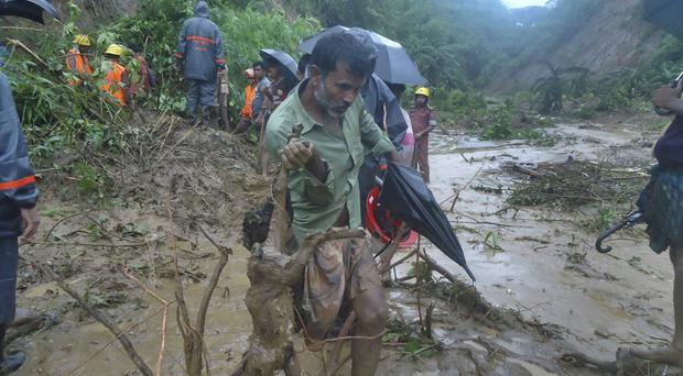 A man carries the carcass of a goat as rescuers search amid the mud after a landslide in Bandarban, Bangladesh (AP)
