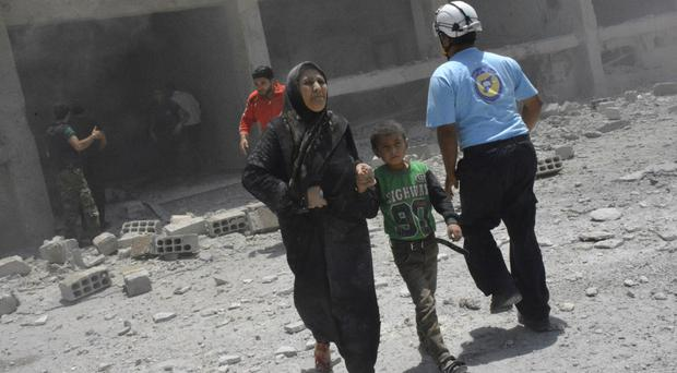 Civilians rush out of damaged buildings after air strikes hit a school housing a number of displaced people (Syrian Civil Defence White Helmets via AP)