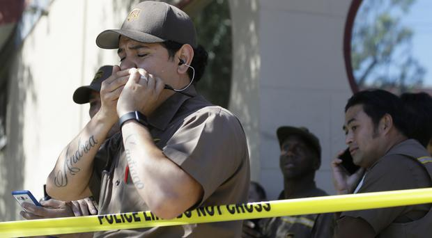 Traumatised UPS workers gather outside the package delivery warehouse where the shooting took place (AP)