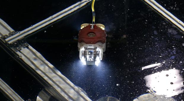 A newly developed robot for underwater investigation at Fukushima reactor moves through the water at a test facility in Yokosuka near Tokyo (AP)