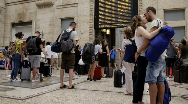 Travellers check departures at a railway station in Milan (AP)
